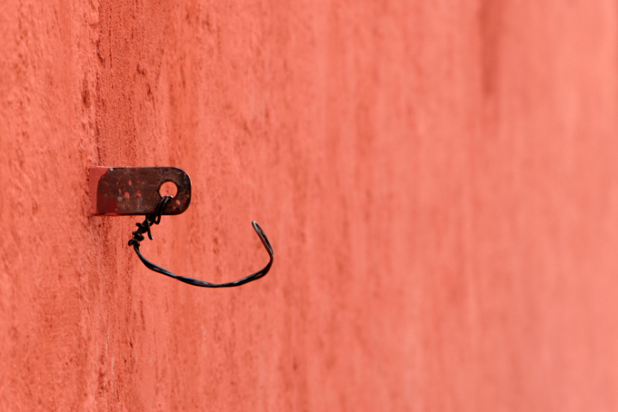 Orange wall with a makeshift metal hook