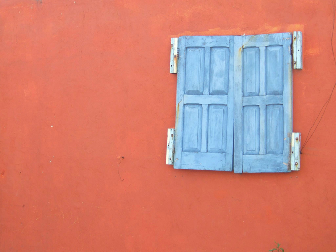 Orange wall with a window with blue shutters