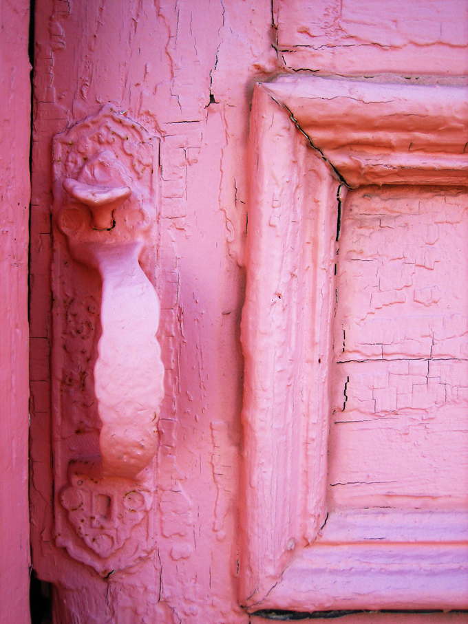 Close up of pink door with cracking paint