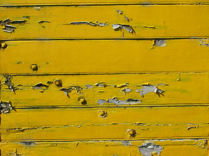 Yellow paint peeling from wooden wall
