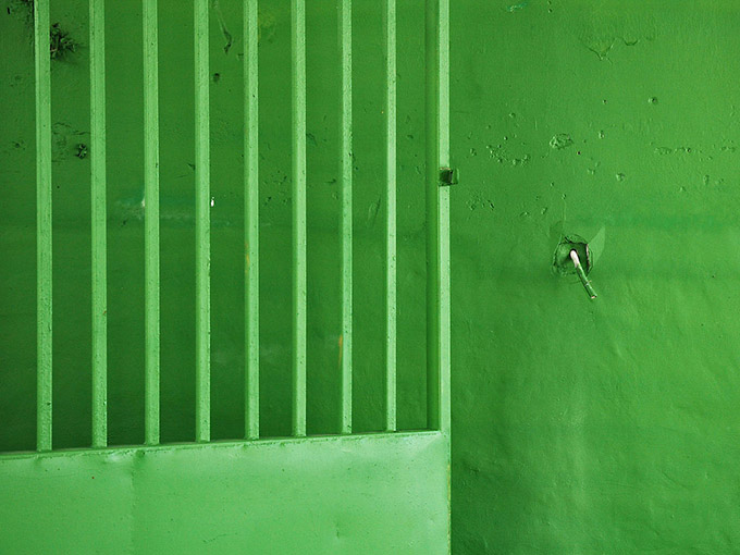 Green grill door against a green wall