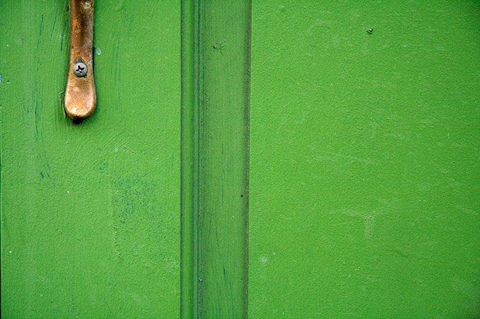 Close up of green wood door an rusting handle