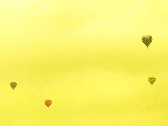 Four hot air balloons against a yellow sky