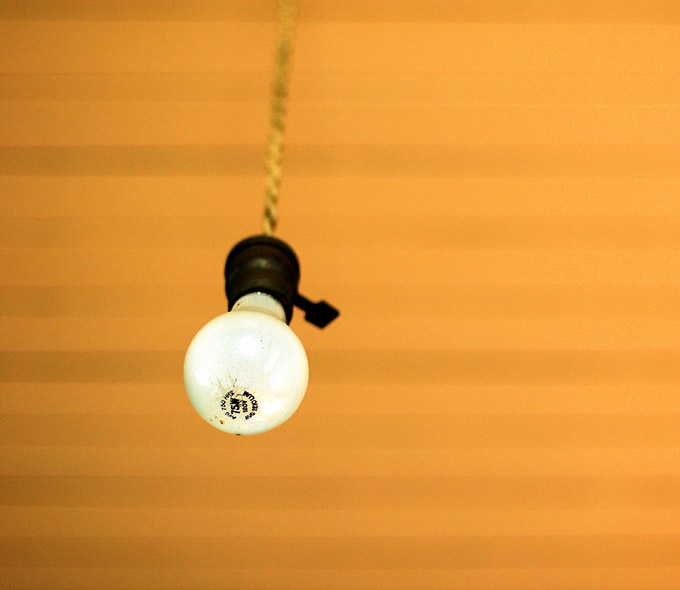 Naked bulb hanging from an orange ceiling