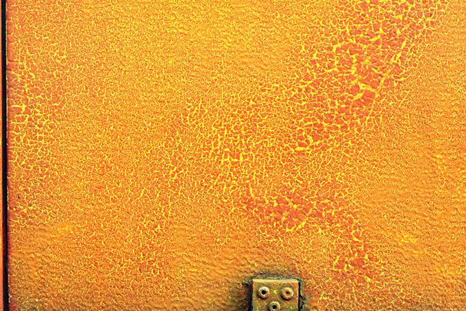 Flaking paint and rust on an orange wall