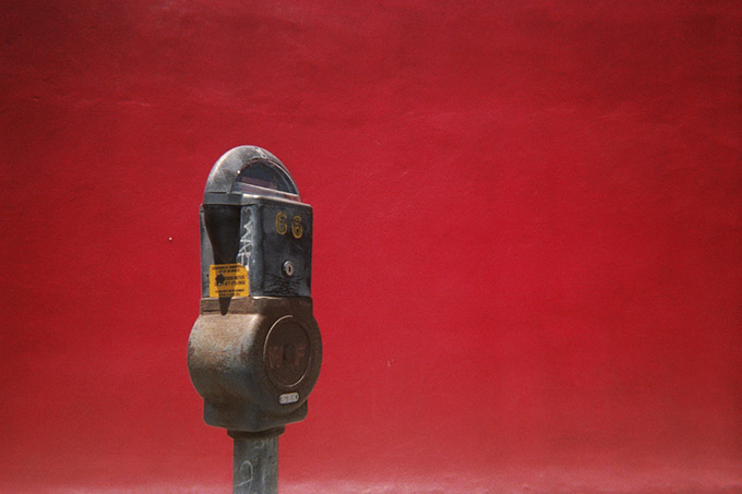 Old parking meter infront of a red wall