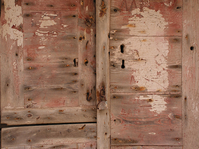 Old aged door with rusted lock and many keyholes