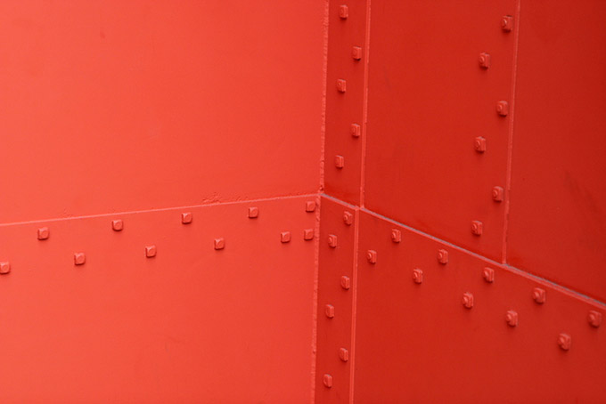 Orange metal wall with rivets