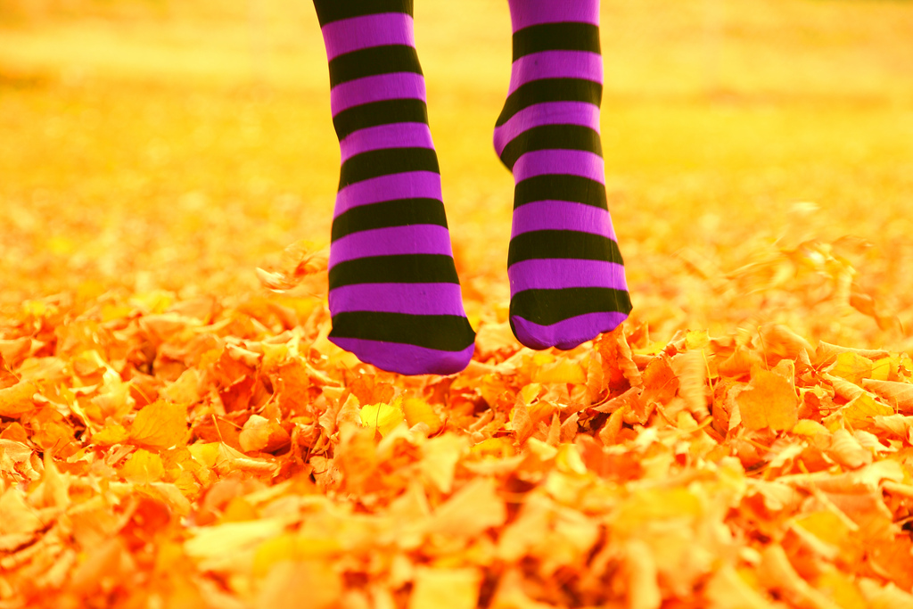 Feet with striped socks jumping over autumn leaves