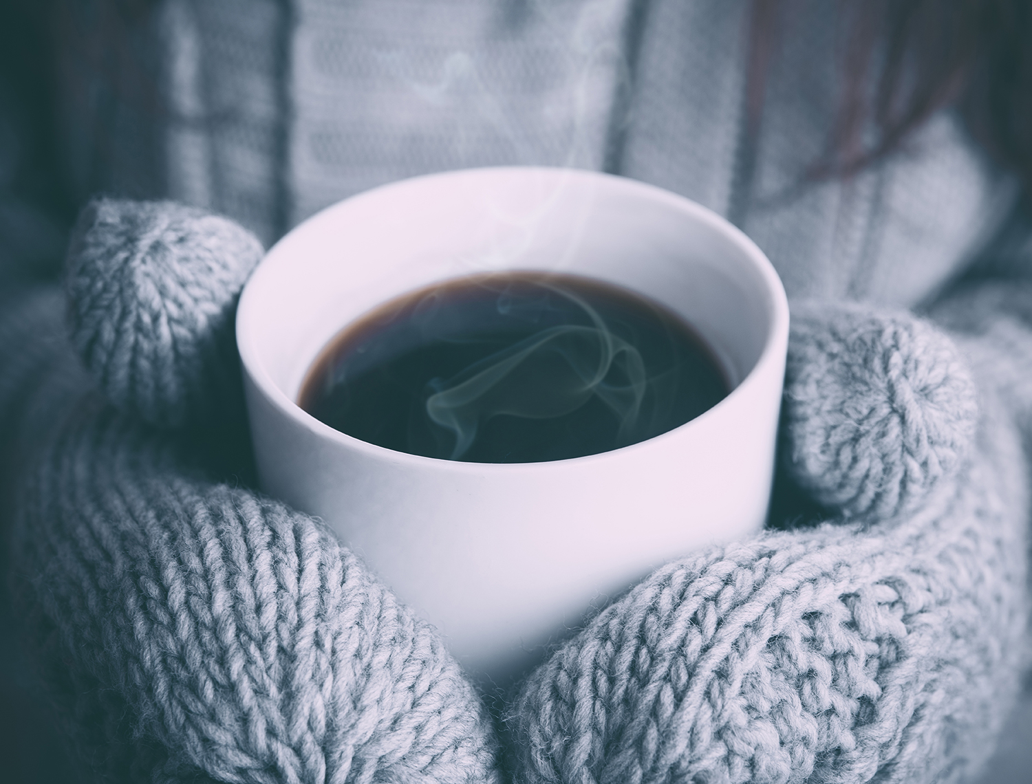 Mitten covered hands holding a coffee cup
